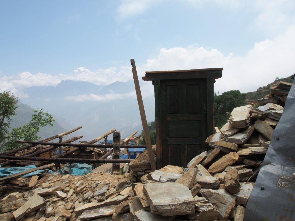 Une porte d'une maison reste debout parmi le débris du village dévasté de Gumba (Gorkha).